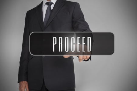 proceed: Businessman selecting label with proceed written on it on grey background