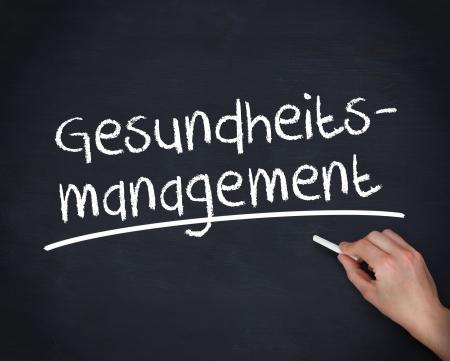 Hand schreiben Deutsch Wörter gesundheits-Management auf einer Tafel