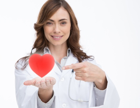 Pretty doctor holding and pointing at a red heart