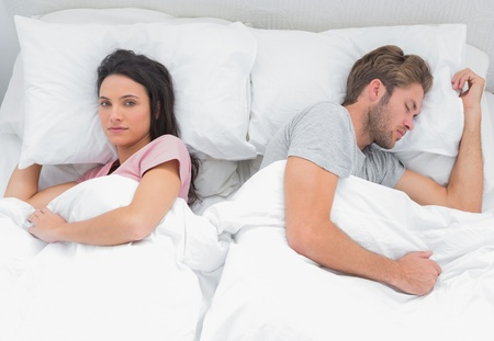 Woman looking at camera while her husband is sleeping in the bed photo