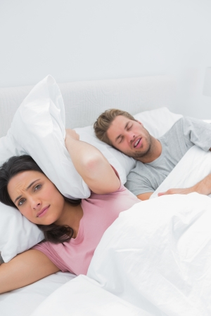 Upset woman covering ears with pillow next to husband snoring next to her photo