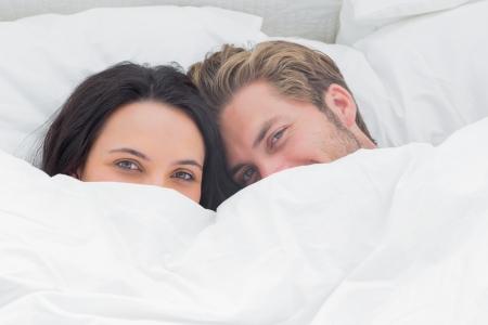 uomo felice: Coppia nascosto sotto il piumone nel loro letto