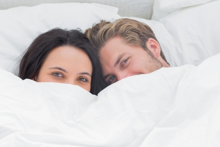 couple home: Couple hiding under the duvet in their bed