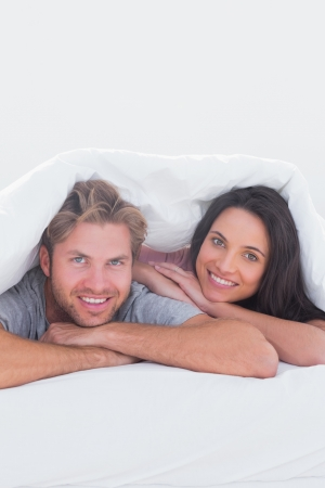 Beautiful couple under the cover in their bed Stock Photo