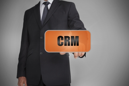 Businessman touching orange tag with the word crm written on it on grey background photo