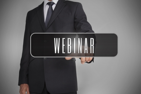 Businessman selecting label with webinar written on it on grey background photo