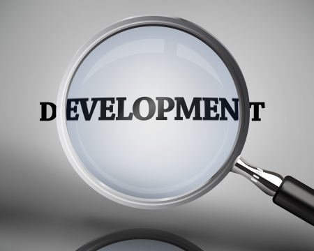 buzz word: Magnifying glass showing development word on grey background