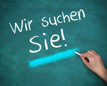Hand writing wir suchen sie on blue background photo
