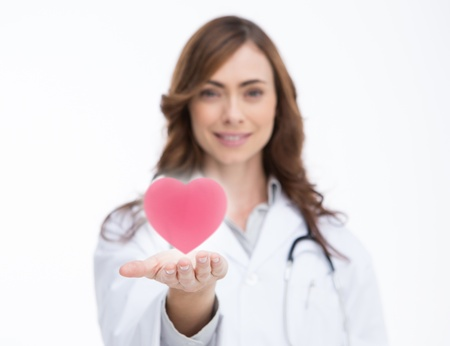 Attractive doctor holding a pink heart Stock Photo