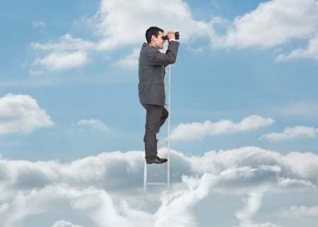 Businessman on ladder over the clouds looking at the horizon with binoculars photo