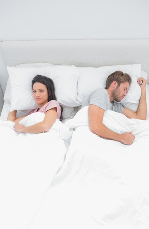 Attractive woman looking at camera while next to her sleeping partner  photo