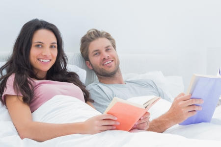 Cheerful couple holding books lying in their bed photo