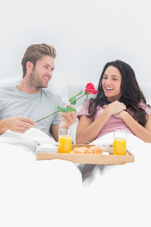 Man giving a rose to his wife during breakfast in bed photo
