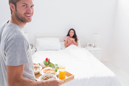 Handsome man bringing breakfast to his wife in bed Stock Photo - 20500410