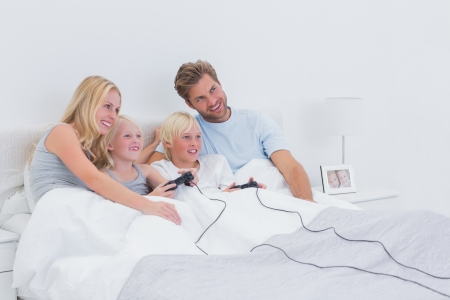 Siblings playing video games with parents watching in bed photo