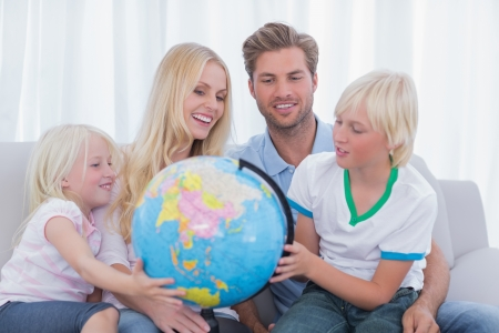 Family looking at globe together in the living room photo