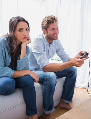 Sad woman annoyed that her partner is playing video games at home on the sofa photo