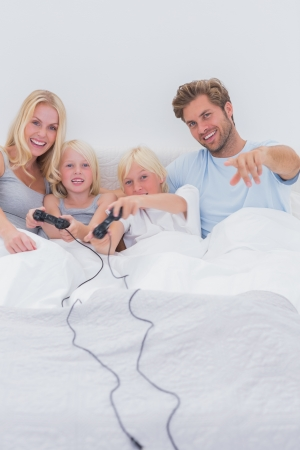 Cheerful family playing video games in bed Stock Photo