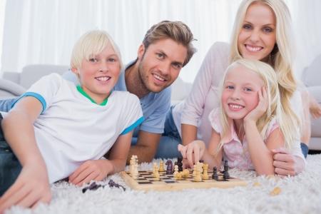 jugando ajedrez: Familia sonriente jugando al ajedrez juntos en la sala de estar