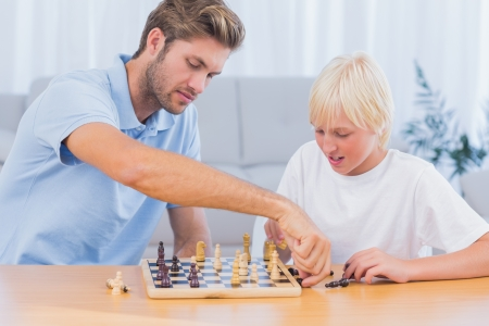 Father and his son playing chess in living room photo