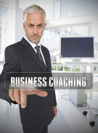 mature business man: Businessman touching the term business coaching in his office