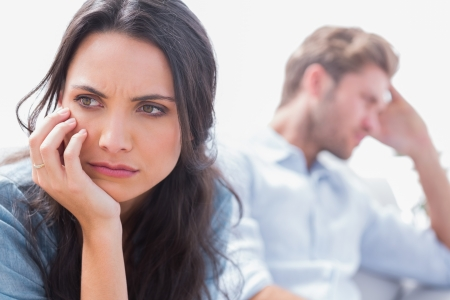 fearful: Annoyed woman holding her head next to her husband Stock Photo