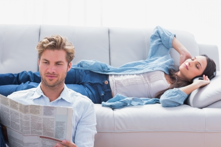 Woman laid on a couch listening to music next to her boyfriend reading a newspaper photo