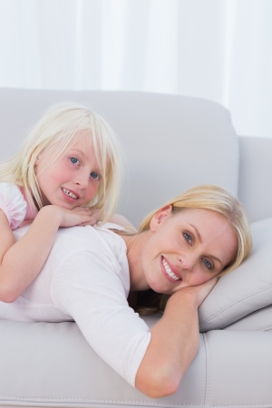 Mother with her daughter lying on couch in the living room photo