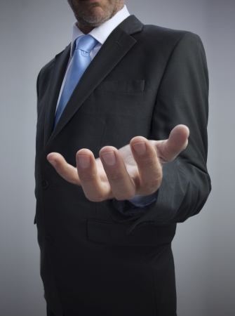 Businessman showing his empty hand against grey background photo