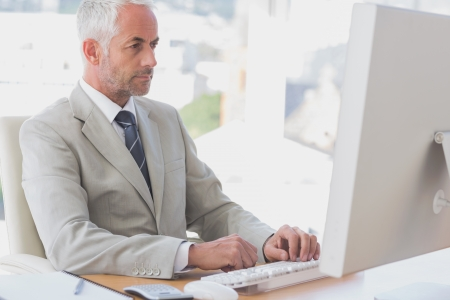 Businessman working at his desk on his computer photo