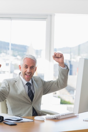 Businessman cheering at his desk in the office Stock Photo - 20634819