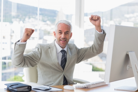 Businessman cheering in his office at his desk Stock Photo - 20637226