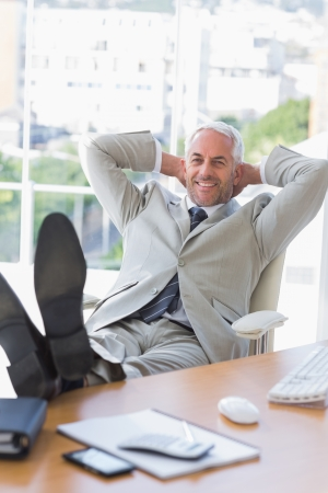 Businessman relaxing at his desk and smiling at camera in the office Stock Photo - 20637632