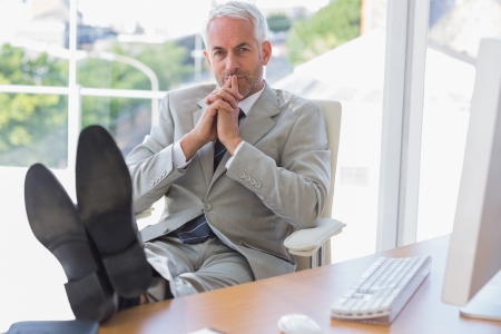 Thoughtful businessman sitting with feet up on his desk in office Stock Photo - 20637681