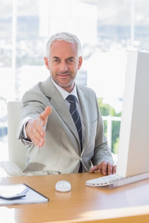 Smiling businessman reaching out for handshake at his desk photo
