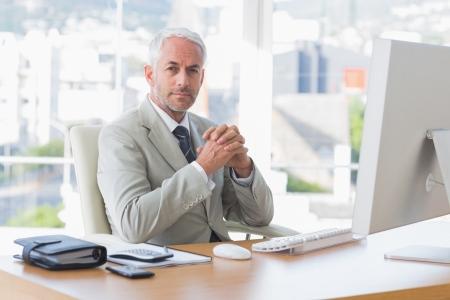Businessman looking at camera sitting at desk Stock Photo - 20636930