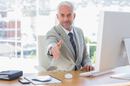 Smiling businessman reaching out hand for handshake at his desk Stock Photo - 20636407