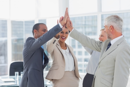 Happy business team high fiving in the office photo