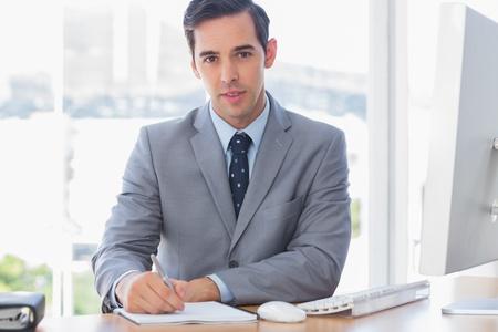 Cheerful businessman writing at his desk and smiling at camera Stock Photo - 20635778