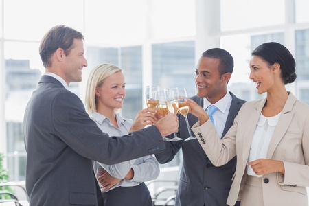 Business team celebrating with champagne and toasting in the office photo