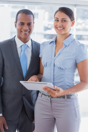 Business team with tablet pc smiling and looking at camera in office Stock Photo - 20617657