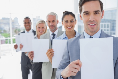 Business team in a line holding blank pages smiling at camera photo