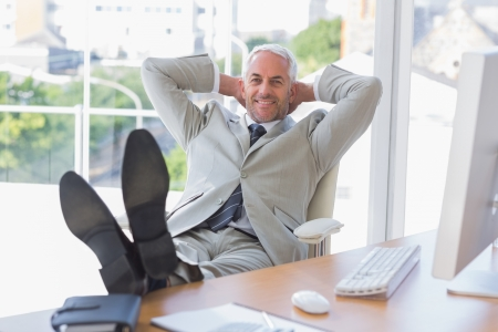 feet on desk: Businessman relaxing at desk and smiling at camera in his office