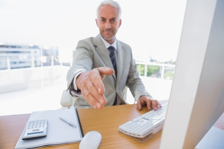 Happy businessman reaching arm out for handshake in his office Stock Photo - 20619114