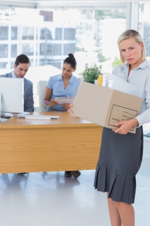 to let: Forlorn businesswoman leaving office after being let go carrying box of things