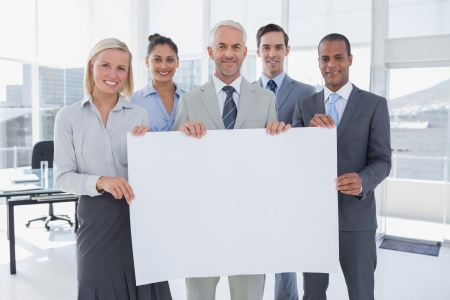 Business team holding large blank poster and smiling at camera photo