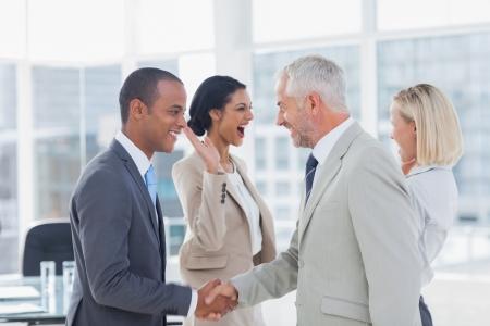 closing business: Equipo de negocios acertado apret�n de manos y una alta fiving en la oficina