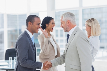 deals: Succesful business team shaking hands and high fiving in the office