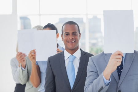 Businessman smiling at camera with colleagues covering faces with white pages photo