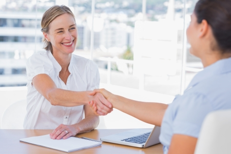 applicant: Smiling interviewer shaking hand of an applicant in her office Stock Photo